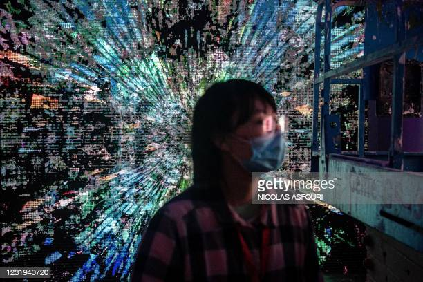 Woman walks in front of a digital painting by Chinese artist Liu Gang at a crypto art exhibition entitled Virtual Niche: Have You Ever Seen Memes in...