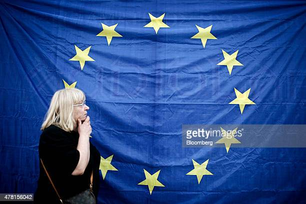 A woman walks in front of a European Union flag during a pro European Union demonstration in Thessaloniki Greece on Monday June 22 2015 After a day...