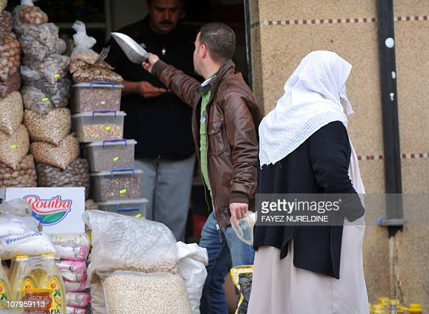 A woman walks in front of a food store after shopping in Quba market in Algiers city on January 10 2011 Algeria began cleaning up today after days of...