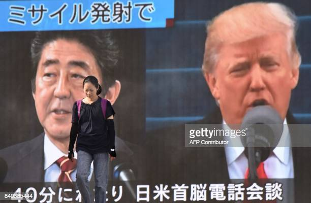 A woman walks in front of a huge screen displaying Japanese Prime Minister Shinzo Abe and US President Donald Trump in Tokyo on August 29 following a...