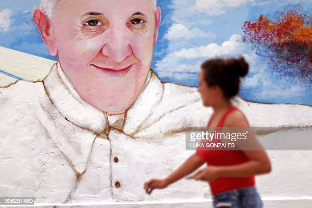 A woman walks in front of a mural depicting Pope Francis in Lima on January 17 2018 Pope Francis will visit the cities of Puerto Maldonado Trujillo...