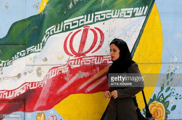 A woman walks in front of a mural painting depicting the Iranian flag in the capital Tehran on August 6 2018 Iranian Foreign Minister Mohammad Javad...