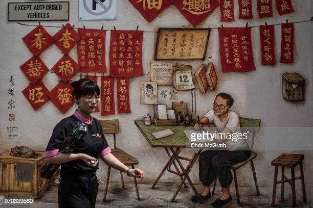 A woman walks in front of a mural showing a Singapore street scene in Chinatown on June 9 2018 in Singapore The historic meeting between US President...