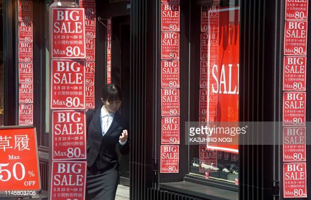 A woman walks in front of a shop displaying notices of discount sale in Tokyo on May 24 2019 Japanese consumer prices rose a sluggish 09 percent last...