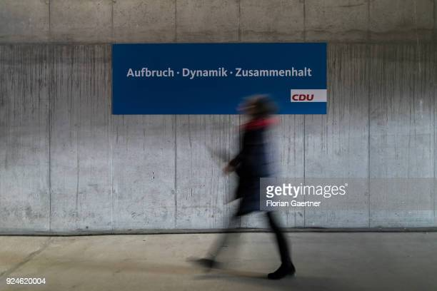 A woman walks in front of a sign with the lettering 'Aufbruch Dynamik Zusammenhalt' at the 30th German Christian Democrats party congress on February...