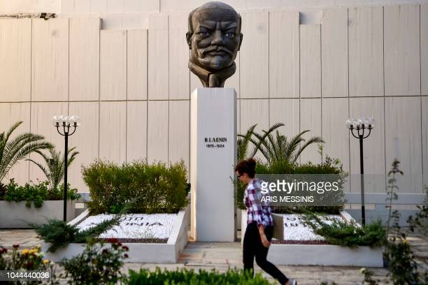 A woman walks in front of a stern bust of Lenin at the yard of the Greek Communist party compound on September 26 2018 The Greek Communist party KKE...