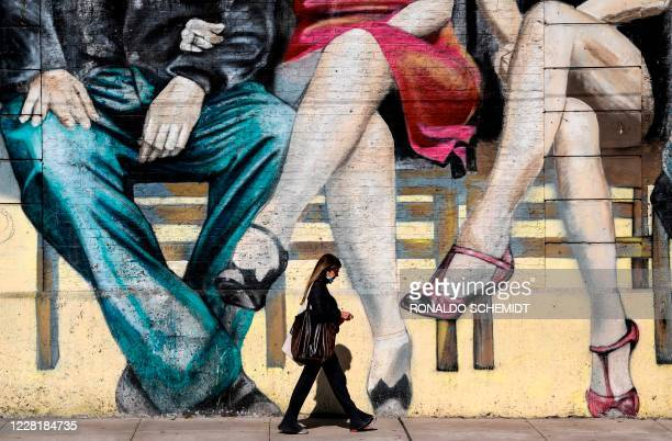 Woman walks in front of a tango related mural in Buenos Aires, on August 24, 2020. - Dancers from all over the world will compete from Wednesday in...