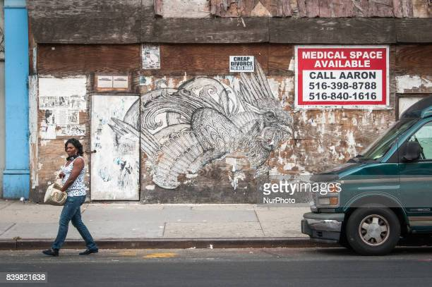 A woman walks in front of a wheat paste street art installment of a rooster in Harlem New York on 10 September 2010
