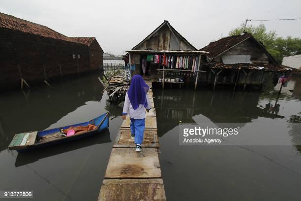 A woman walks in front of her waterlogged home in Sriwulan village Sayung subdistrict of Demak regency Central Java Indonesia on February 2 2018...