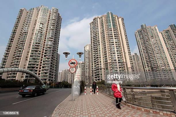 A woman walks in front of high rise residential buildings in Shanghai China on Monday Jan 17 2011 Shanghai China's financial center will this year...