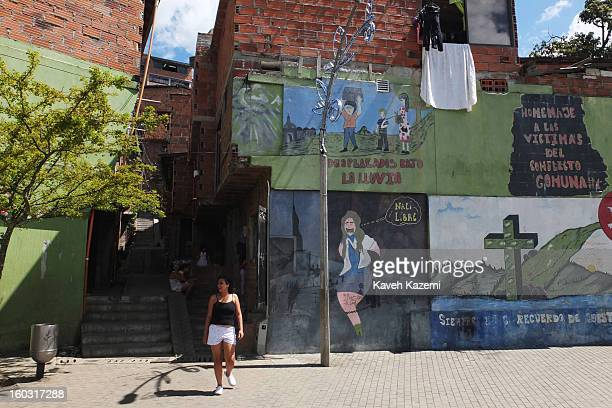 A woman walks in front of murals depicting troubled times and present days in the slums in the urban spaces constructed near Spain Library built for...