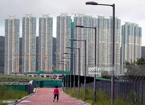 A woman walks in front of residential tower blocks in the Tseung Kwan O area of the New Territories in Hong Kong China on Tuesday Sept 4 2012 Hong...