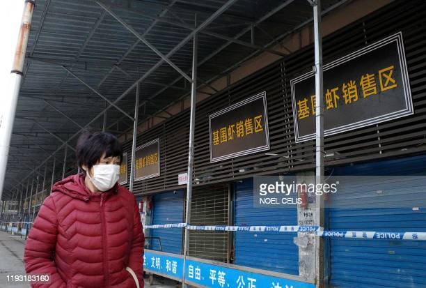A woman walks in front of the closed Huanan wholesale seafood market where health authorities say a man who died from a respiratory illness had...