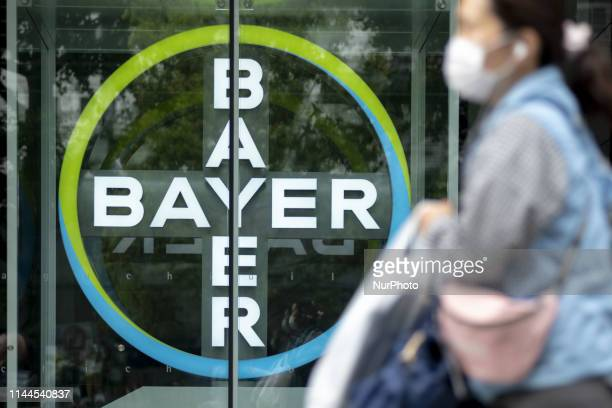 A woman walks in front of the coroporation Bayer May 18 2019 in Tokyo