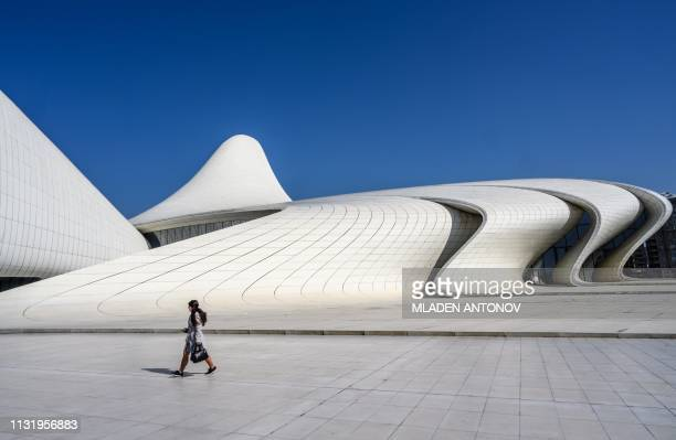 A woman walks in front of the Heydar Aliyev Center in Baku on March 22 2019 The building was designed by IraqiBritish architect Zaha Hadid and is...