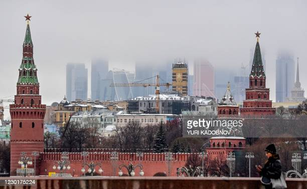 Woman walks in front of the Kremlin and skyscrapers of the Moscow International Business Centre in Moscow on December 17, 2020.