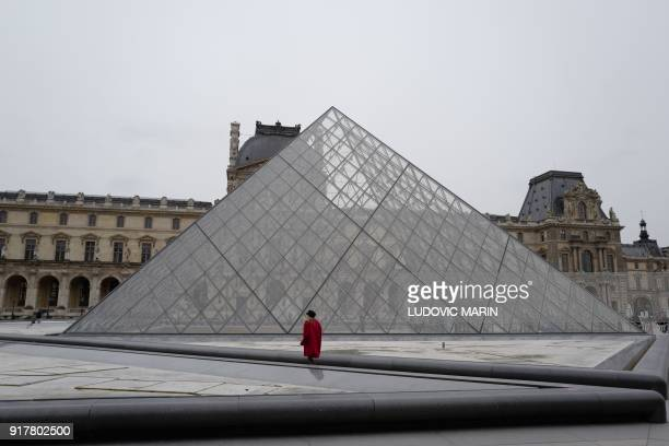 Woman walks in front of the Pyramid of the Louvre on February 13 in Paris.