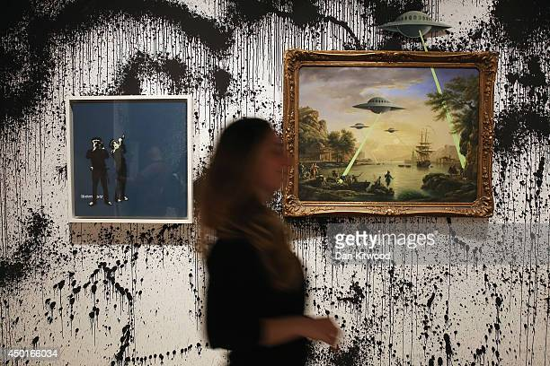Woman walks in front of two pieces of work entitled 'UFO' and 'Avon and Somerset Constabulary' during a press preview of the first unauthorized...