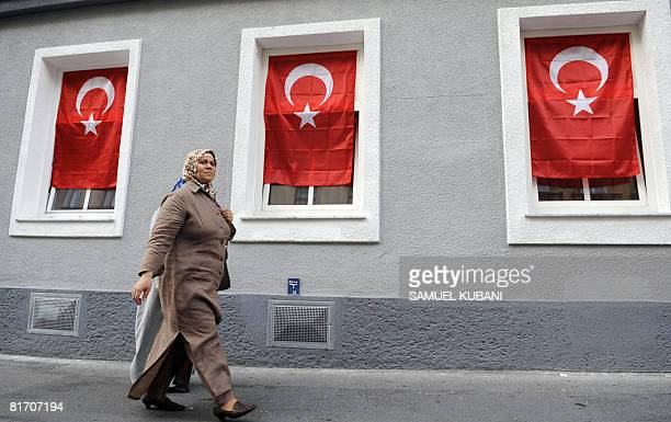A woman walks in front of windows decorated with Turkish flags a few hours before the Euro 2008 Championships semifinal match Germany vs Turkey on...
