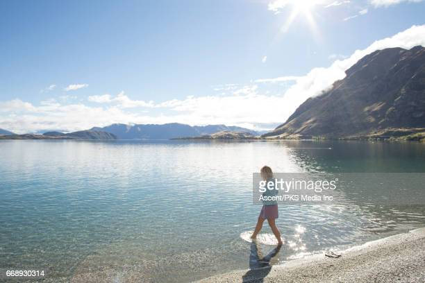 Woman walks in lake shallows, at sunrise