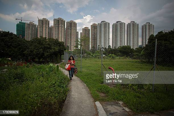 A woman walks in Ma Shi Po Village on July 11 2013 in Hong Kong China The North East New Territories New Development Areas project proposed by HKSAR...