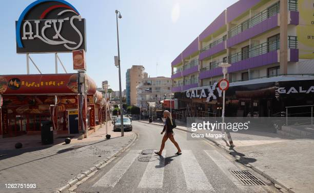 Woman walks in Punta Ballena street at Magaluf on July 30, 2020 in Mallorca, Spain. The United Kingdom, whose citizens comprise the largest share of...