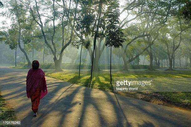 A woman walks in the Dhaka University campus on a winter morning Dhaka Bangladesh November 27 2007