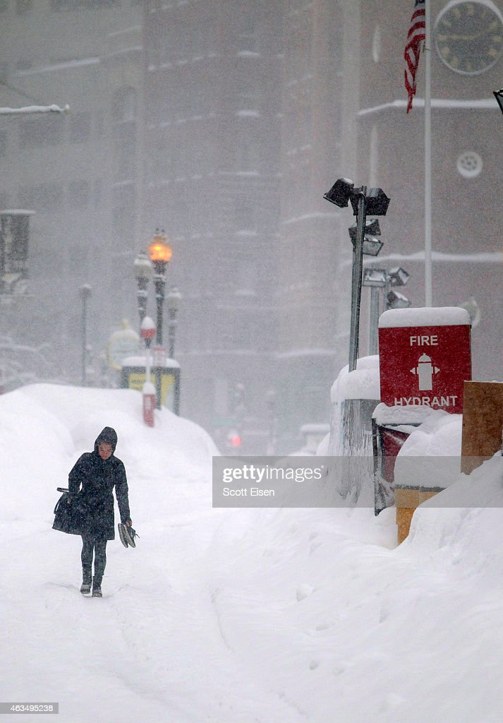 A woman walks in the Downtown Crossing section during winter storm Neptune which dropped over a foot of snow February 15, 2015 in Boston, Massachusetts. This is the fourth major storm to hit the New England region that has already seen more than 6 feet of snow in some areas.