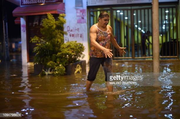A woman walks in the inundated street of the Botafogo neighborhood after a strong rain flooded multiple areas of the city of Rio de Janeiro Brazil on...