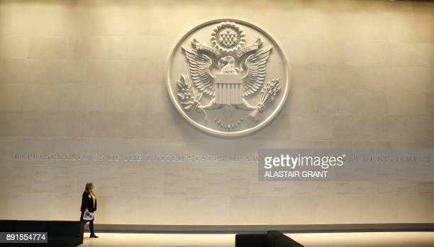 A woman walks in the main lobby entrance featuring a large Department of State embossed seal along with all the names of the United States...