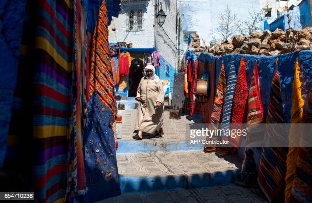 A woman walks in the Medina of the northwestern Moroccan city of Chefchouen in the northern Rif region on September 19 2017 Huddling against a...