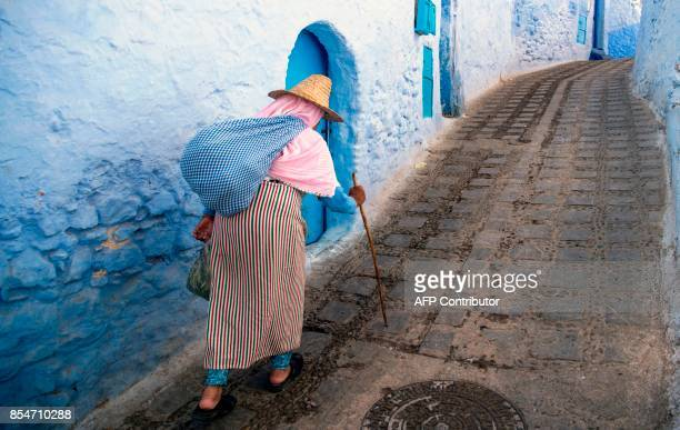 A woman walks in the Medina of the northwestern Moroccan city of Chefchouen in the northern Rif region on September 21 2017 Huddling against a...