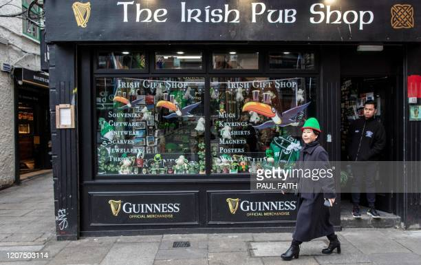 A woman walks in the popular Temple bar area of Dublin on March 17 as St Patrick's Day festivities are cancelled and pubs shut in reaction to the...