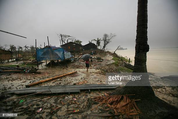 A woman walks in the rain May 15 in the outskirts of Yangon Myanmar It has been estimated that more than 100000 people were killed by Cyclone Nargis...