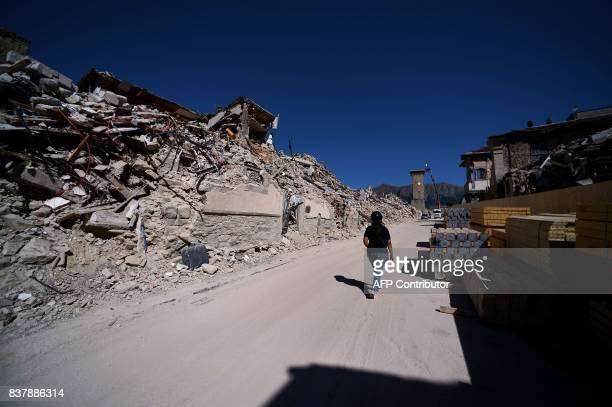 TOPSHOT A woman walks in the remains of Amatrice on August 23 2017 a year after a deadly earthquake left nearly 300 people dead and destroyed the...