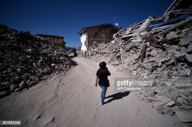 A woman walks in the remains of Amatrice on August 23 2017 a year after a deadly earthquake left nearly 300 people dead and destroyed the small town...