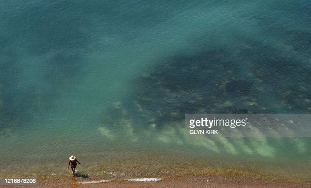 TOPSHOT A woman walks in the sea on Saltdean beach near Brighton on the south coast of England on June 2 2020 following a further relaxation of the...