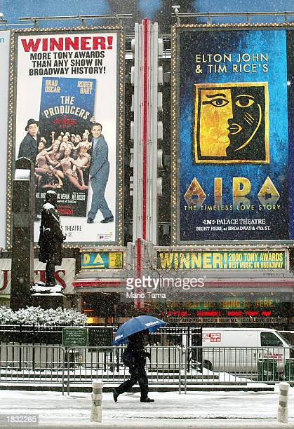 A woman walks in the snow in Times Square beneath signs for the Broadway productions 'Aida' and 'The Producers' March 6 2003 in New York City About...