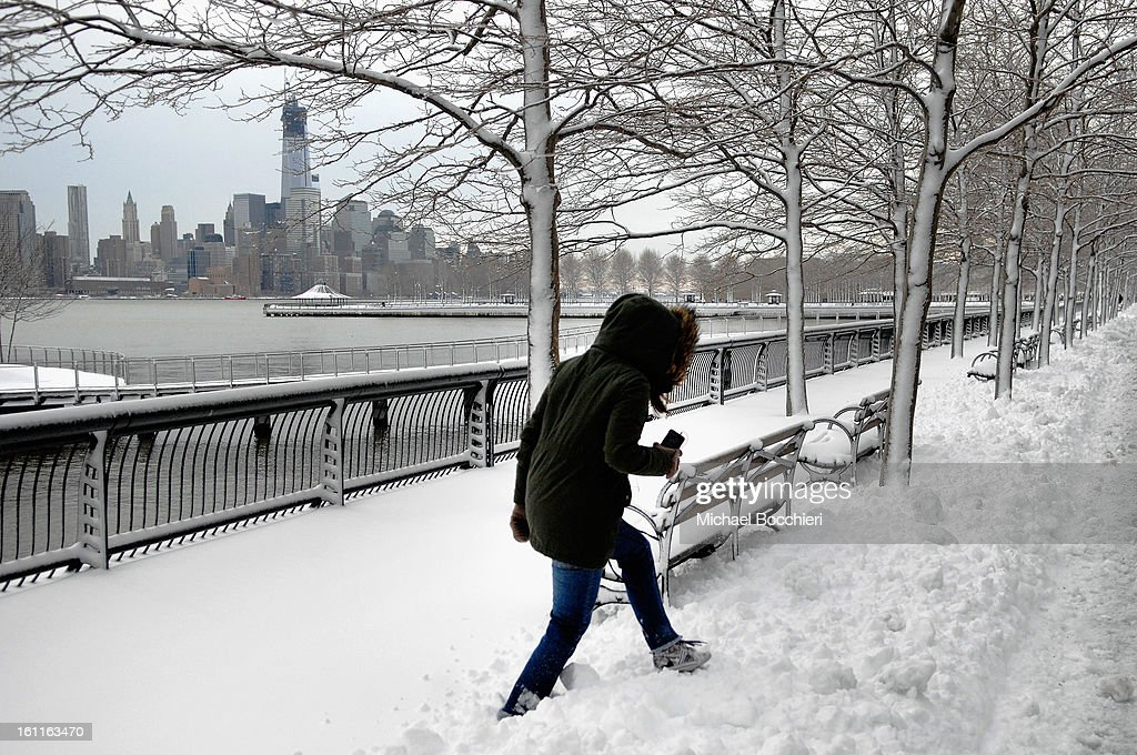 A woman walks in the snow with the World Trade Center in the background following a major winter storm on February 9, 2013 in Hoboken, New Jersey. Much of the Northeast received a foot or more of snow through Saturday morning with possible record-setting blizzard conditions expected. Heavy snow warnings are in effect from New Jersey through southern Maine.