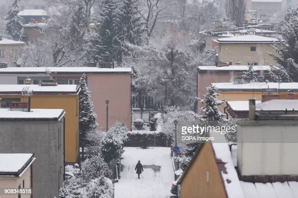 A woman walks in the street between snow covered buildings during winter in Krakow