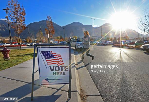 A woman walks into a polling center to vote in the midterm elections as the morning sun rises over the Utah Wasatch Mountains on November 6 2018 in...