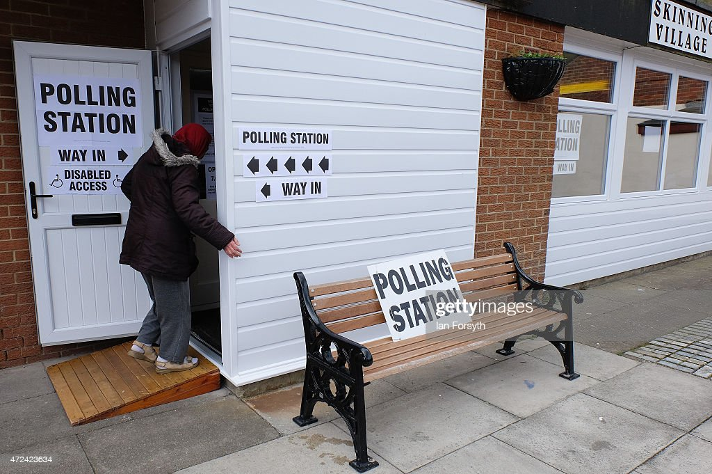 A woman walks into a polling station set up inside the Village Hall on May 7, 2015 in Skinningrove, England. The United Kingdom has gone to the polls to vote for a new government in one of the most closely fought General Elections in recent history. With the result too close to call it is anticipated that there will be no overall clear majority winner and a coalition government will have to be formed once again.