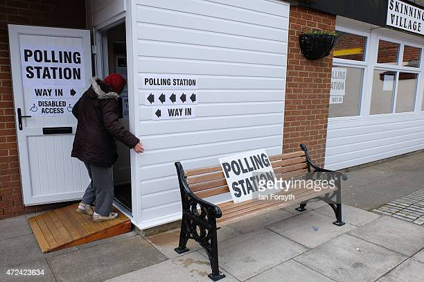 A woman walks into a polling station set up inside the Village Hall on May 7 2015 in Skinningrove England The United Kingdom has gone to the polls to...