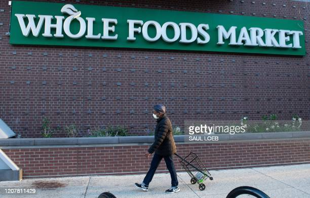 Woman walks into a Whole Foods supermarket during hours reserved for customers 60 years and older to minimize contact with others as people social...