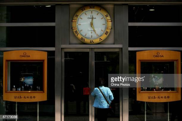 A woman walks into an Omega watch shop on March 24 2006 in Beijing China According to state media China announced on March 21 its plan to impose a...