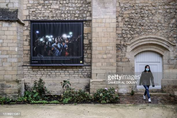 Woman walks near a picture by Japanese photographer Yasuyoshi Chiba, recipient of the 2020 World Press Photo of the Year, displayed on a wall as part...