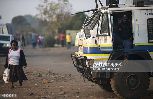 A woman walks near a policeman speaking on the phone as he sits in police truck in Gugulethu township east of Johannesburg on May 7 2014 South...