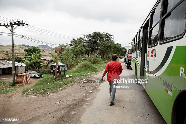 A woman walks near a public transit bus in the Dilma Rousseff favela of Rio de Janeiro Brazil on Monday July 6 2015 As the fastest inflation in more...