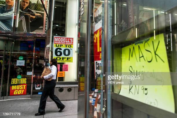 A woman walks near a retail store closing in Times Square on August 8 2020 in New York City With more than four months NYC has closed some of their...