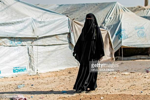 A woman walks near tents at the Kurdishrun alHol camp for the displaced where families of Islamic State foreign fighters are held in the alHasakeh...